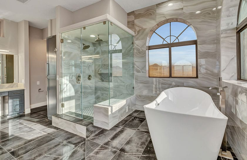 Beautiful modern bathroom with large tub, glass shower, and marble floors and walls