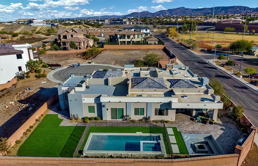 Drone photo of a large Las Vegas home with beautiful landscaping and pool.