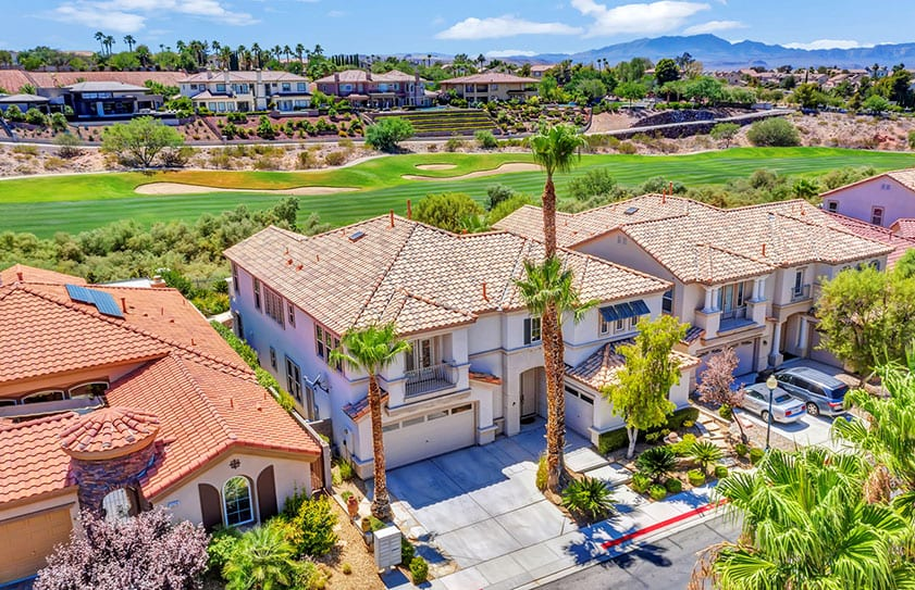 Drone photo of a home for sale with views of a golf course and Las Vegas mountains
