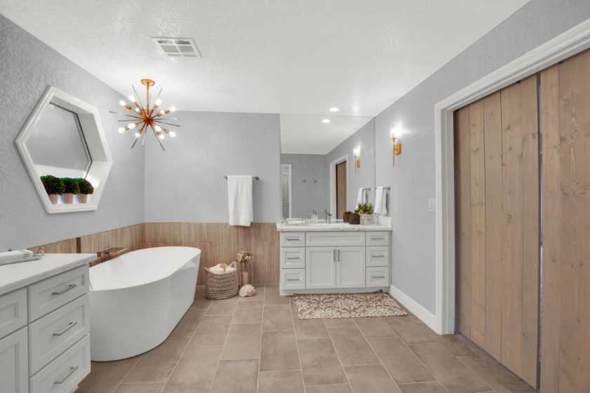 bathroom with tub and modern light fixture