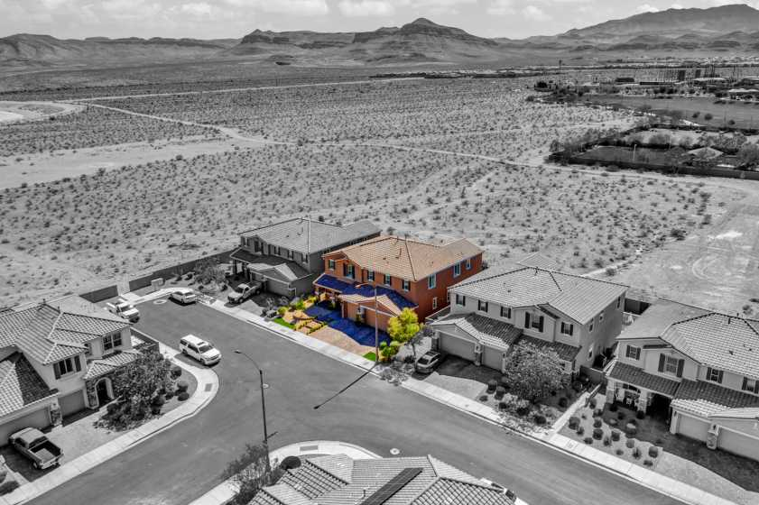 drone photo of house in desert with house highlighted and the rest of the picture is black and white.